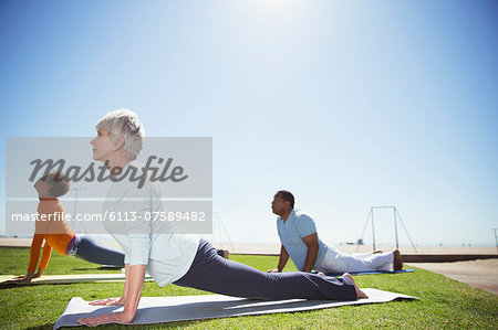 Seniors practicing yoga in sunny beach park Stock Photo - Premium Royalty-Free, Image code: 6113-07589482