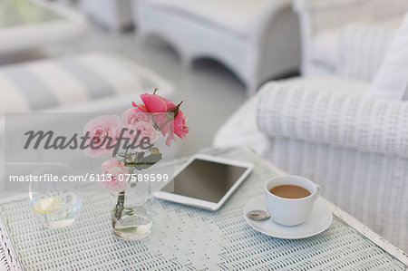 Pink roses on patio table with coffee cup and digital tablet Stock Photo - Premium Royalty-Free, Image code: 6113-07589599