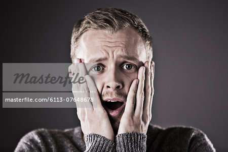 Portrait of surprised man with head in hands Stock Photo - Premium Royalty-Free, Image code: 6113-07648678