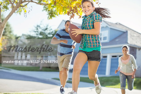Family playing football in sunny street Stock Photo - Premium Royalty-Free, Image code: 6113-07648790
