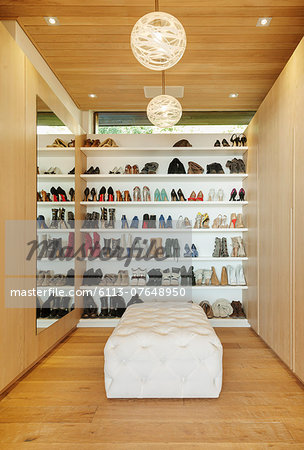 Modern walk-in closet with shoes on shelves Stock Photo - Premium Royalty-Free, Image code: 6113-07648950
