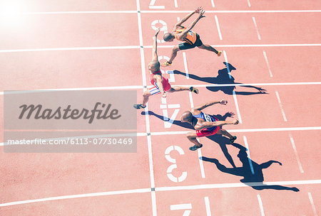 Runners crossing finish line on track Stock Photo - Premium Royalty-Free, Image code: 6113-07730469