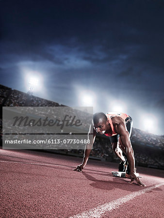 Runner poised at starting line on track Stock Photo - Premium Royalty-Free, Image code: 6113-07730488