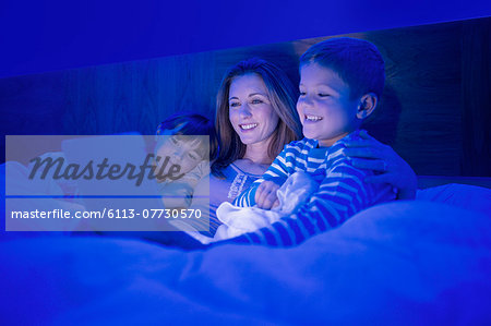 Mother and children using digital tablet in bed Stock Photo - Premium Royalty-Free, Image code: 6113-07730570