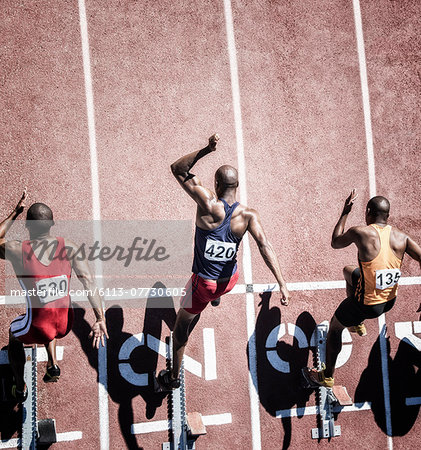 Sprinters taking off from starting block Stock Photo - Premium Royalty-Free, Image code: 6113-07730605