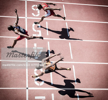 Runners crossing finish line on track Stock Photo - Premium Royalty-Free, Image code: 6113-07730615