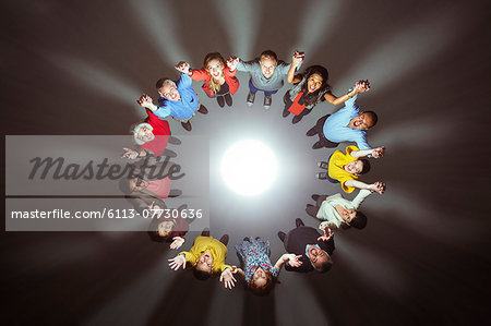 Diverse crowd around bright light Stock Photo - Premium Royalty-Free, Image code: 6113-07730636