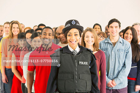 Portrait of smiling policewoman in front of large crowd Stock Photo - Premium Royalty-Free, Image code: 6113-07730656