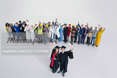 Workforce cheering behind confident graduates Stock Photo - Premium Royalty-Free, Image code: 6113-07730685