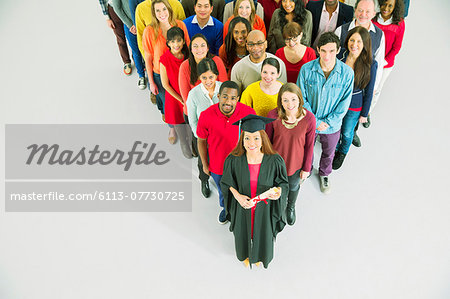 Diverse crowd behind confident graduate Stock Photo - Premium Royalty-Free, Image code: 6113-07730725