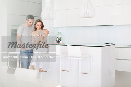 Couple using digital tablet in kitchen Stock Photo - Premium Royalty-Free, Image code: 6113-07730747
