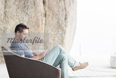 Man sitting in modern armchair Stock Photo - Premium Royalty-Free, Image code: 6113-07730767