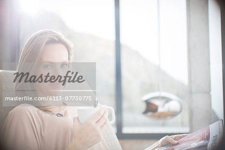 Woman having cup of coffee on sofa Stock Photo - Premium Royalty-Free, Image code: 6113-07730775