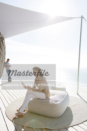 Woman using digital tablet on modern balcony Stock Photo - Premium Royalty-Free, Image code: 6113-07730804