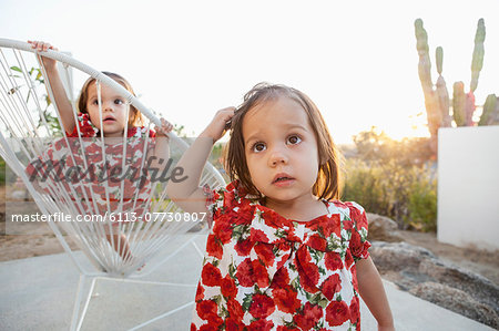 Twin baby girls playing on patio Stock Photo - Premium Royalty-Free, Image code: 6113-07730807
