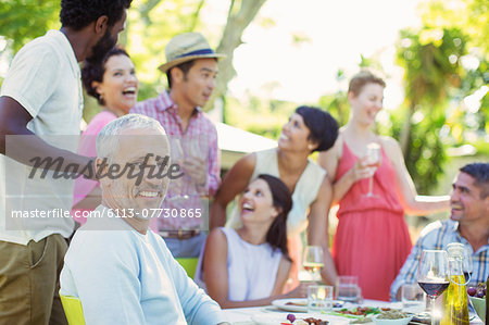 Man smiling at party outdoors Stock Photo - Premium Royalty-Free, Image code: 6113-07730865