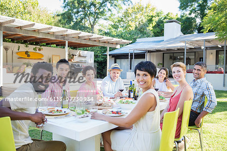 Friends smiling at table outdoors Stock Photo - Premium Royalty-Free, Image code: 6113-07730934