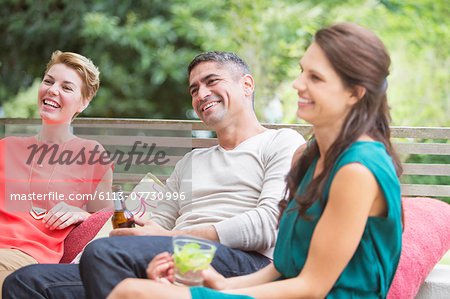 Friends relaxing together outdoors Stock Photo - Premium Royalty-Free, Image code: 6113-07730996