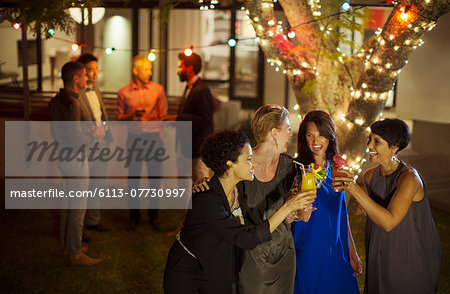 Friends toasting each other at party Stock Photo - Premium Royalty-Free, Image code: 6113-07730997