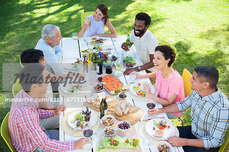 Friends talking at table outdoors Stock Photo - Premium Royalty-Free, Image code: 6113-07731001