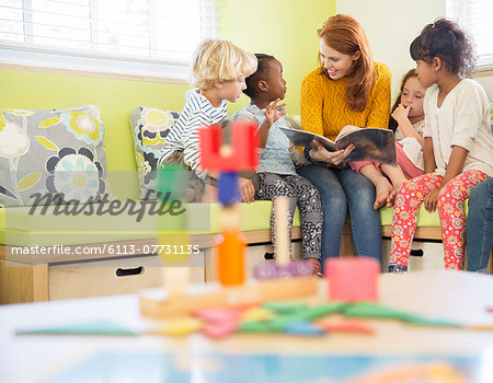 Teacher and students reading in classroom Stock Photo - Premium Royalty-Free, Image code: 6113-07731135