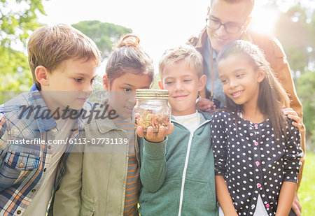 Student and teacher examining insects in jar outdoors Stock Photo - Premium Royalty-Free, Image code: 6113-07731139