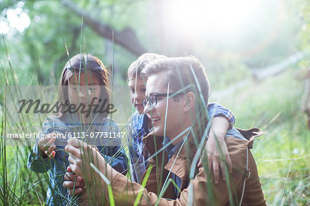 Students and teacher examining grass in forest Stock Photo - Premium Royalty-Free, Image code: 6113-07731147