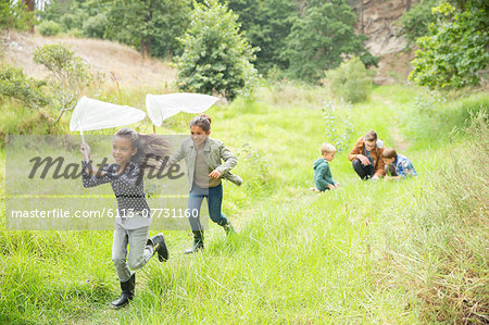 Children playing with butterfly nets on dirt path Stock Photo - Premium Royalty-Free, Image code: 6113-07731160