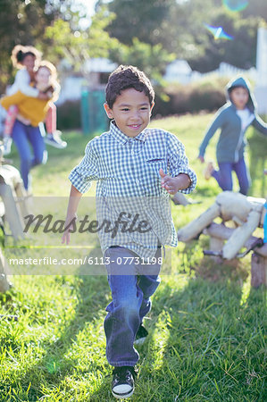 Boy walking in grass outdoors Stock Photo - Premium Royalty-Free, Image code: 6113-07731198