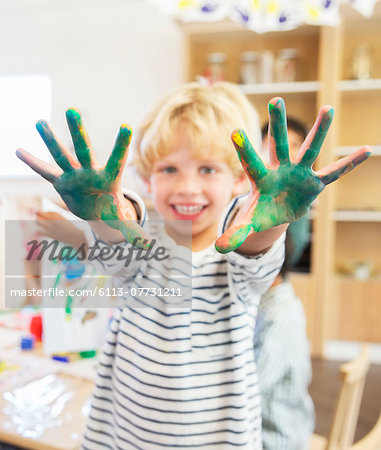 Student showing off messy hands in classroom Stock Photo - Premium Royalty-Free, Image code: 6113-07731211