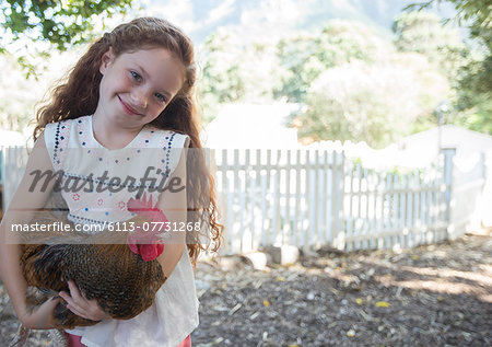 Girl holding chicken at petting zoo Stock Photo - Premium Royalty-Free, Image code: 6113-07731268