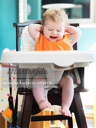 Baby girl crying in high chair Stock Photo - Premium Royalty-Free, Image code: 6113-07731332