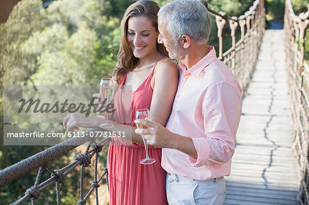 Couple toasting each other on wooden rope bridge Stock Photo - Premium Royalty-Free, Image code: 6113-07731531