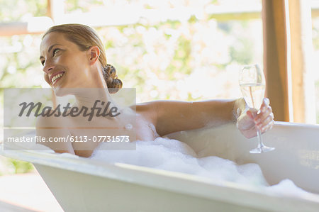 Woman having champagne in bubble bath Stock Photo - Premium Royalty-Free, Image code: 6113-07731573