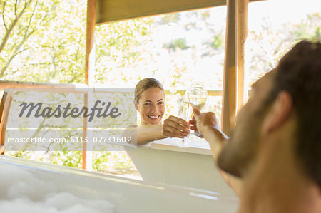 Couple toasting each other in bubble baths Stock Photo - Premium Royalty-Free, Image code: 6113-07731602