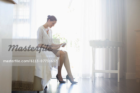 Businesswoman using digital tablet in hotel room Stock Photo - Premium Royalty-Free, Image code: 6113-07731637