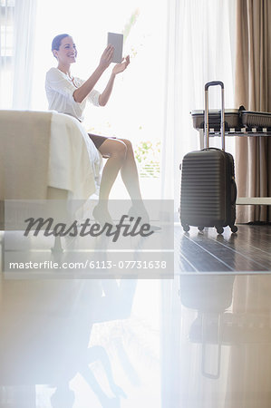 Businesswoman using digital tablet in hotel room Stock Photo - Premium Royalty-Free, Image code: 6113-07731638