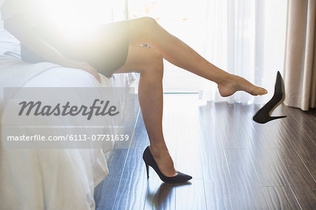 Businesswoman kicking off her shoes in hotel room Stock Photo - Premium Royalty-Free, Image code: 6113-07731639