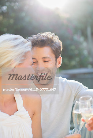 Couple toasting each other with champagne together outdoors Stock Photo - Premium Royalty-Free, Image code: 6113-07731647