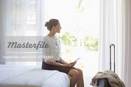 Businesswoman using digital tablet in hotel room Stock Photo - Premium Royalty-Free, Image code: 6113-07731655