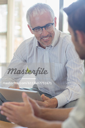Businessmen talking in office Stock Photo - Premium Royalty-Free, Image code: 6113-07731671