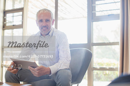 Businessman using digital tablet in living room Stock Photo - Premium Royalty-Free, Image code: 6113-07731693