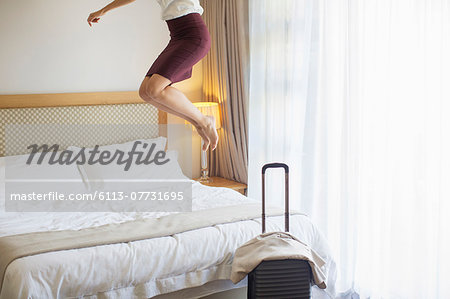 Businesswoman jumping on bed in hotel room Stock Photo - Premium Royalty-Free, Image code: 6113-07731695