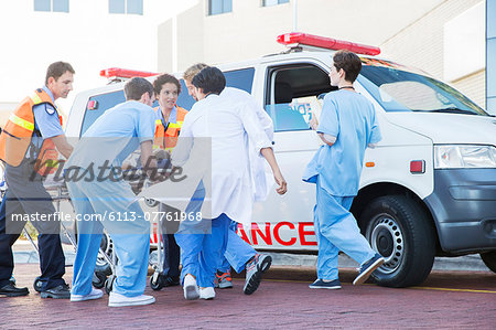 Doctors, nurses, and paramedic examining patient on stretcher Stock Photo - Premium Royalty-Free, Image code: 6113-07761968