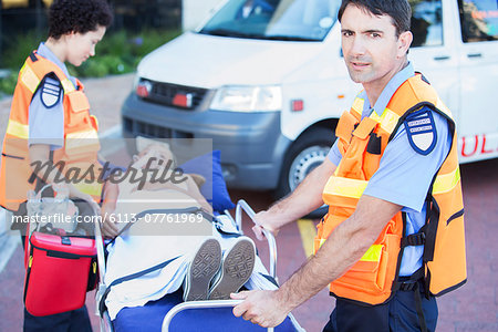 Paramedics wheeling patient on stretcher in hospital parking lot Stock Photo - Premium Royalty-Free, Image code: 6113-07761969