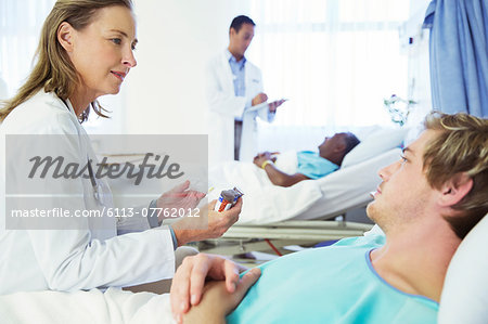 Doctor explaining medication to patient in hospital Stock Photo - Premium Royalty-Free, Image code: 6113-07762012