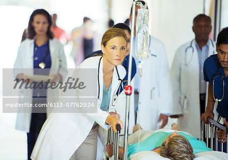 Doctors and nurses wheeling patient in hospital hallway Stock Photo - Premium Royalty-Free, Image code: 6113-07762024
