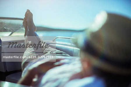 Man relaxing on boat near beach Stock Photo - Premium Royalty-Free, Image code: 6113-07762113