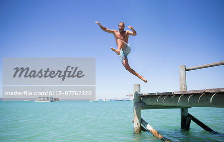 Couple jumping off wooden dock into water Stock Photo - Premium Royalty-Free, Image code: 6113-07762120