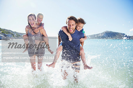 Family running in water on beach Stock Photo - Premium Royalty-Free, Image code: 6113-07762162